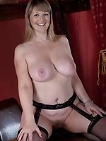 Sophie UK enjoys dressing in an evening gown with a pair of stockings and garter belt, especially if her fans are watching.  She takes out her large n
